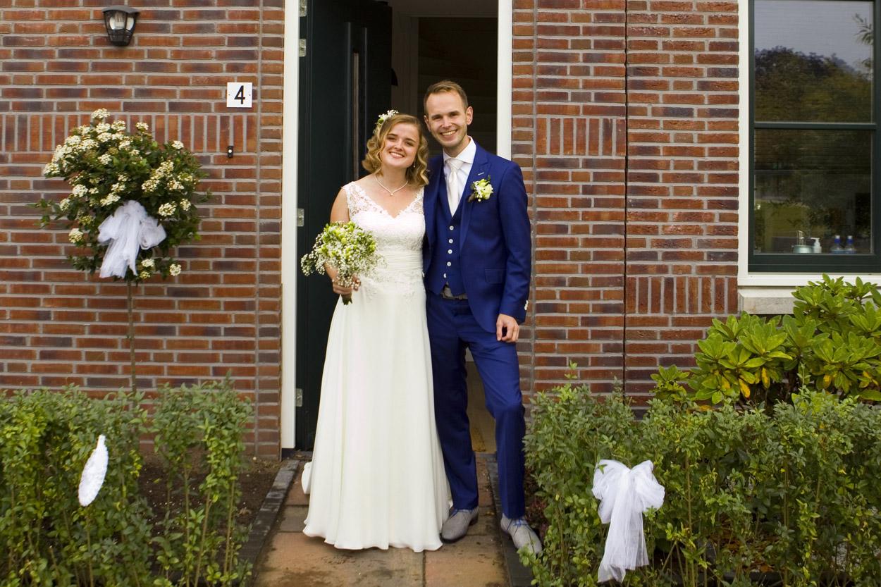 Bruidsfotografie bruiloft bruidspaar in deuropening huis Huis ter Heide