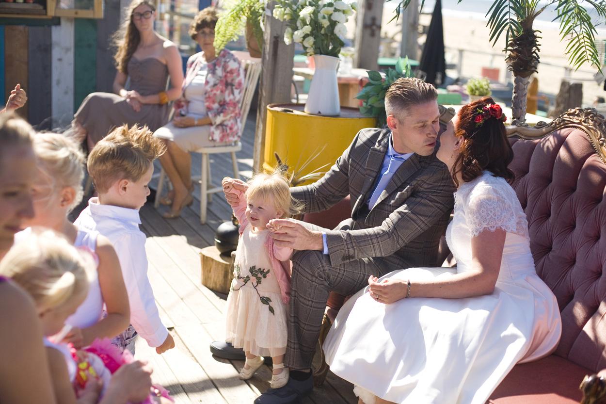 Spontane bruidsfotografie bruiloft ceremonie kus bruidspaar kindjes strandbruiloft trouwreportage Beachclub Indigo Scheveningen