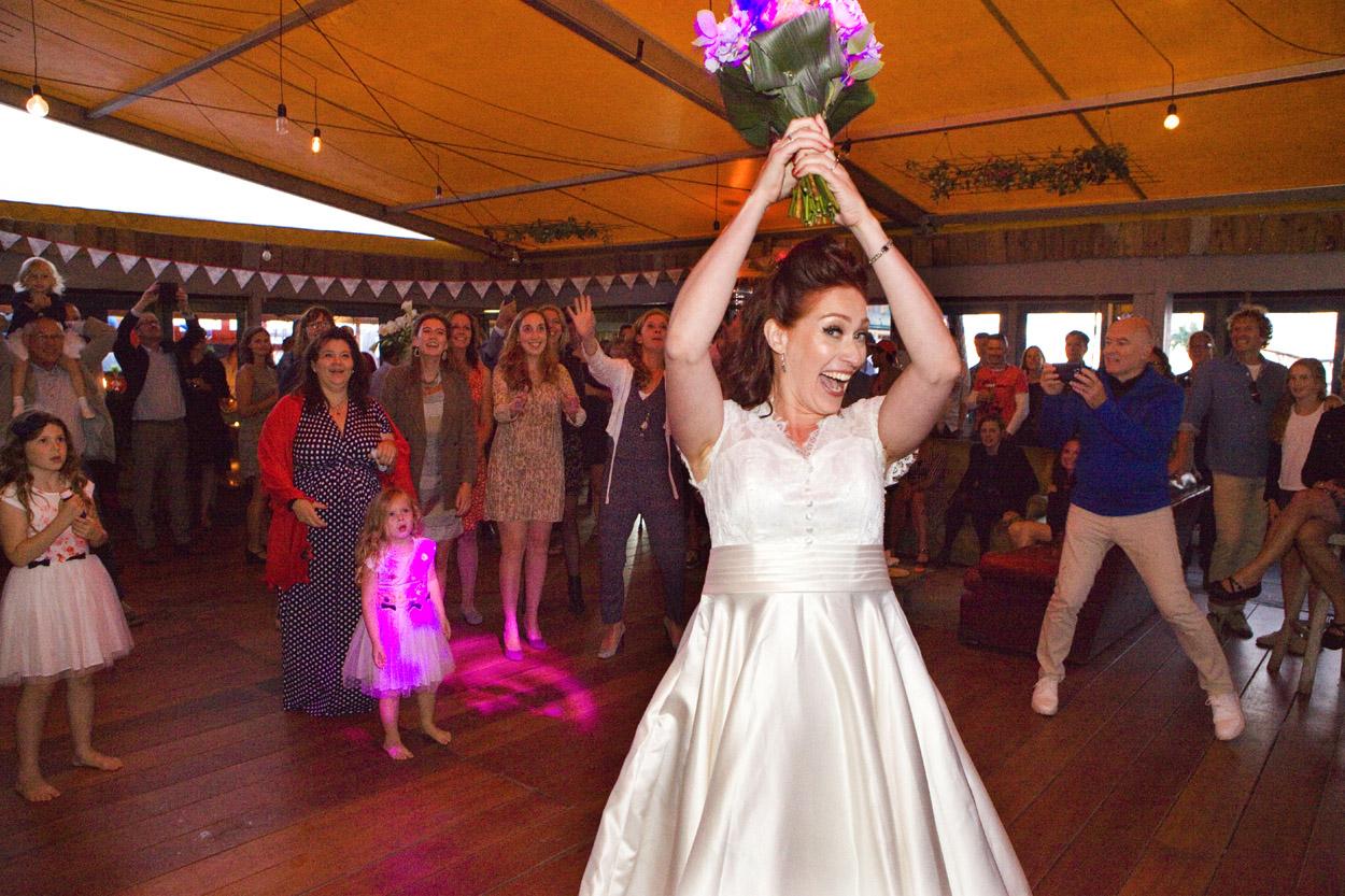 Spontane bruidsfotografie bruiloft trouwfeest boeket gooien strandbruiloft trouwreportage Beachclub Indigo Scheveningen