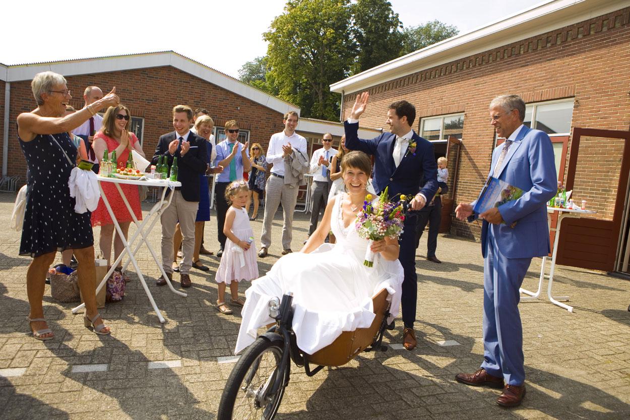 Spontane trouwfoto's bruidsfotografie bruiloft bruidspaar vertrek bakfiets zwaaien Katwijk aan Zee