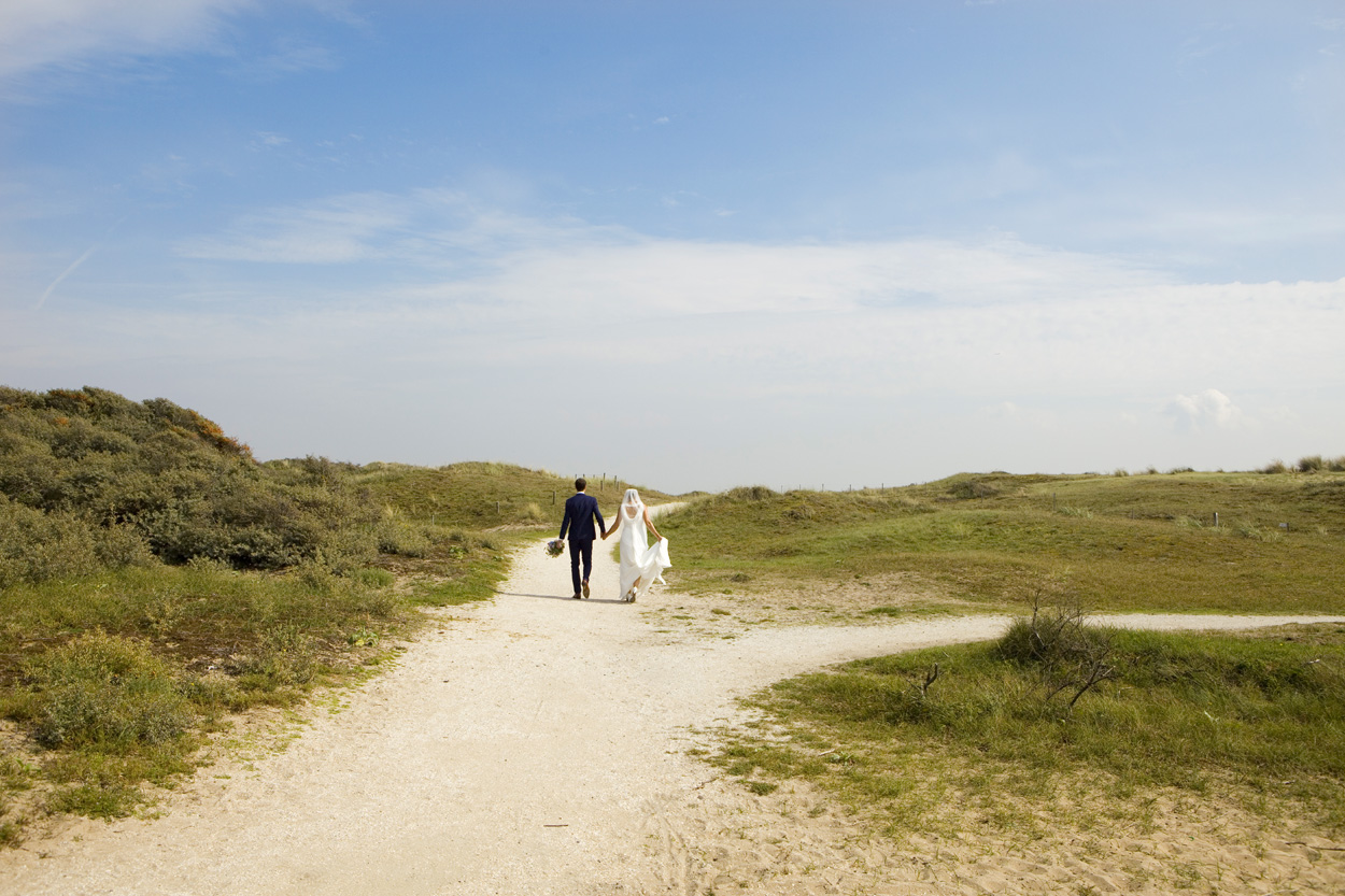 Spontane trouwfoto's bruidsfotografie bruiloft trouwreportage bruidspaar wandeling duinen Katwijk aan Zee