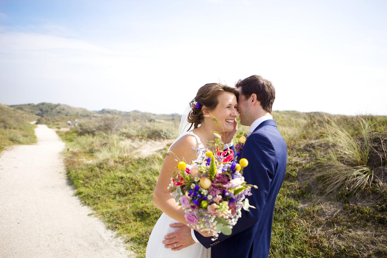 Spontane trouwfoto's bruidsfotografie bruiloft trouwreportage bruidspaar fluisteren duinen Katwijk aan Zee