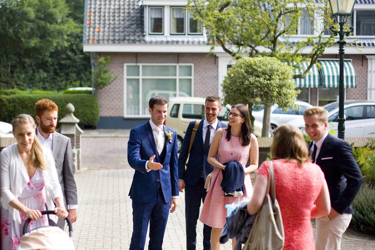 Spontane trouwfoto's bruidsfotografie bruidegom ontvangst gasten Joannes de Doperkerk Katwijk aan Zee