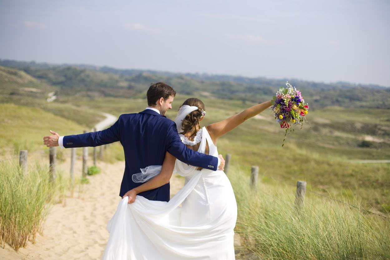 Spontane trouwfoto's bruidsfotografie bruiloft trouwreportage bruidspaar wandeling uitzicht duinen Katwijk aan Zee