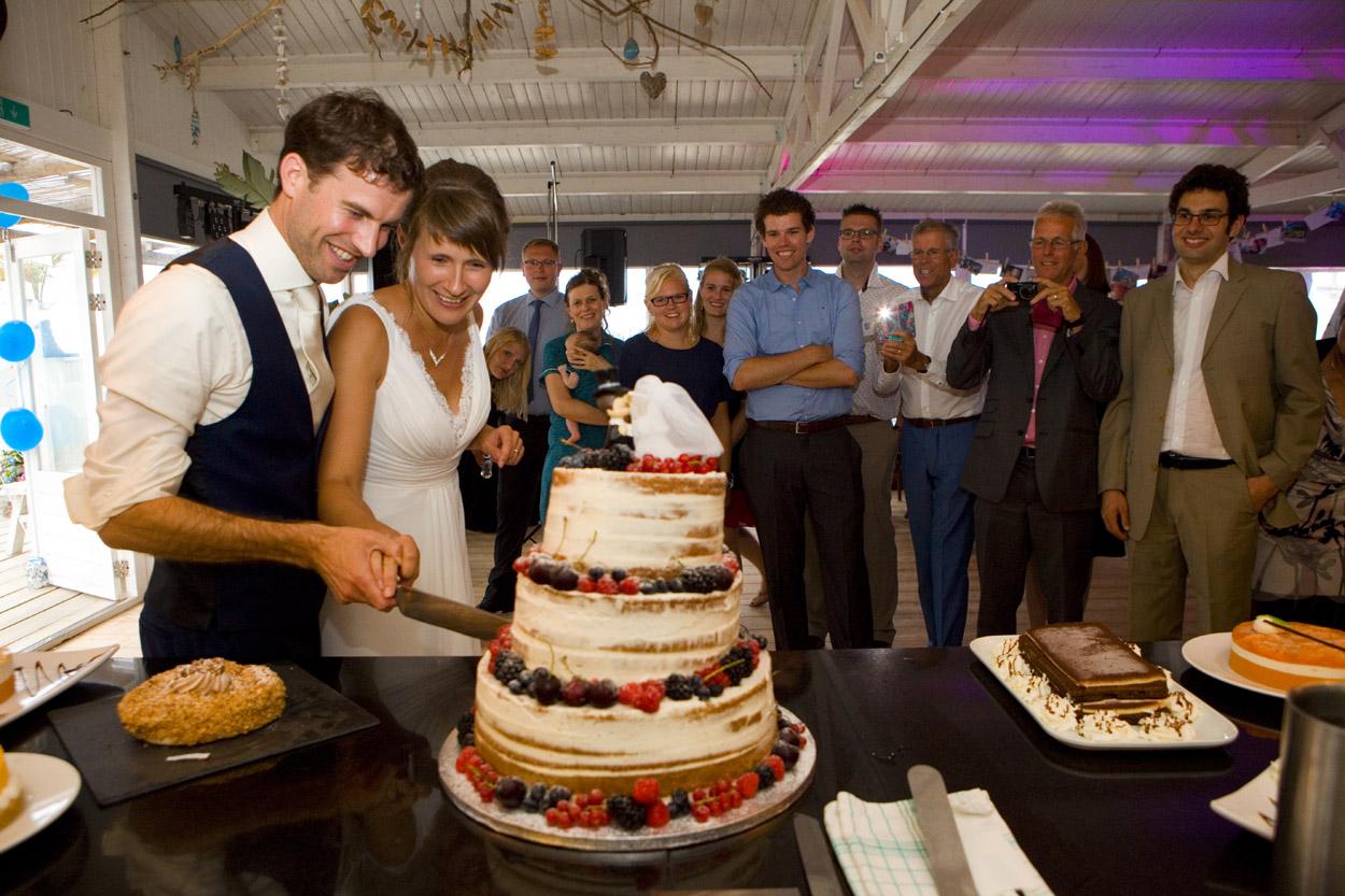 Spontane trouwfoto's bruidsfotografie bruiloft bruidspaar bruidstaart aansnijden Willie Zuid Katwijk aan Zee