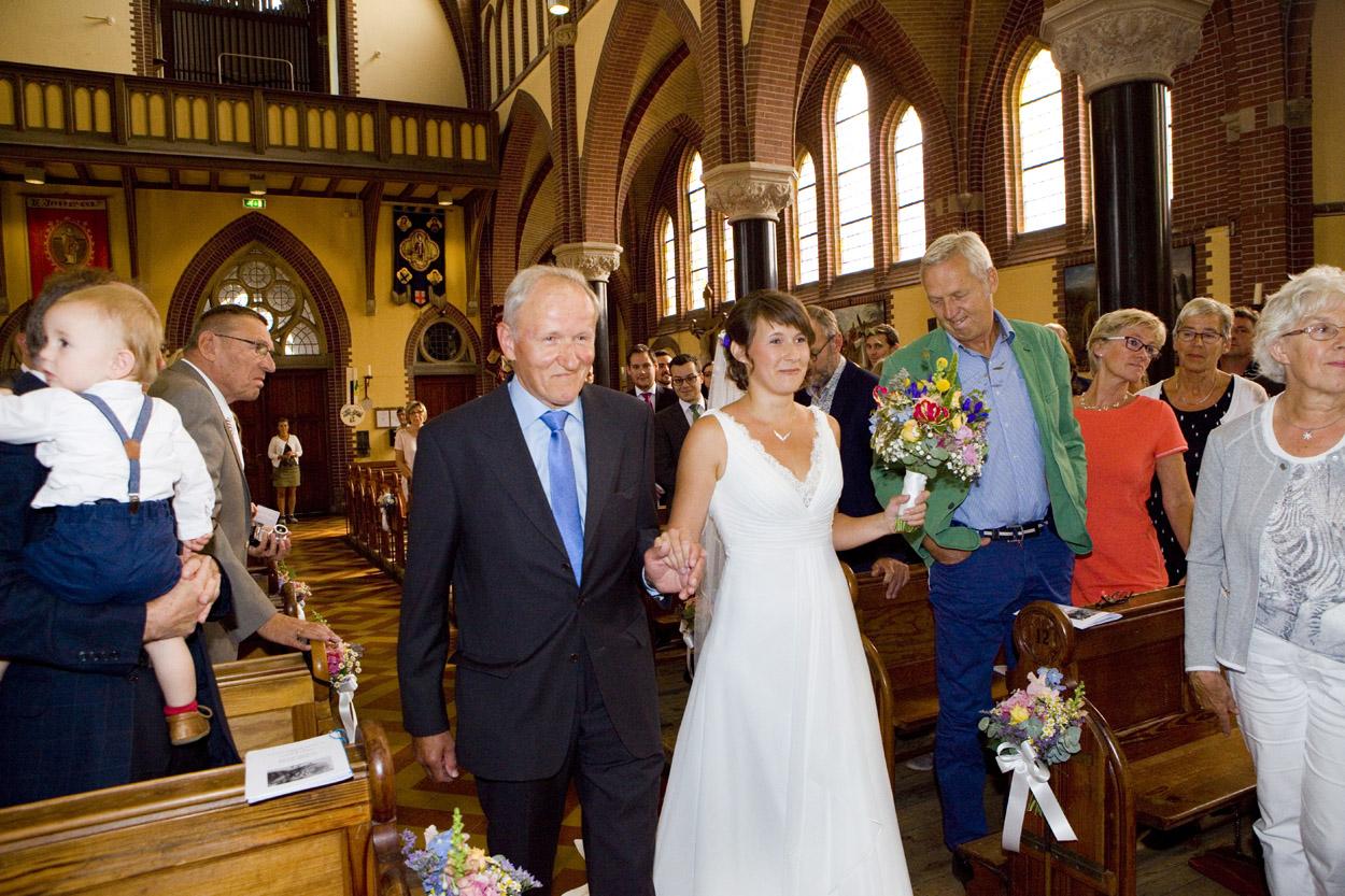 Spontane trouwfoto's bruidsfotografie bruiloft entree bruid met vader kerkelijke inzegening Joannes de Doper