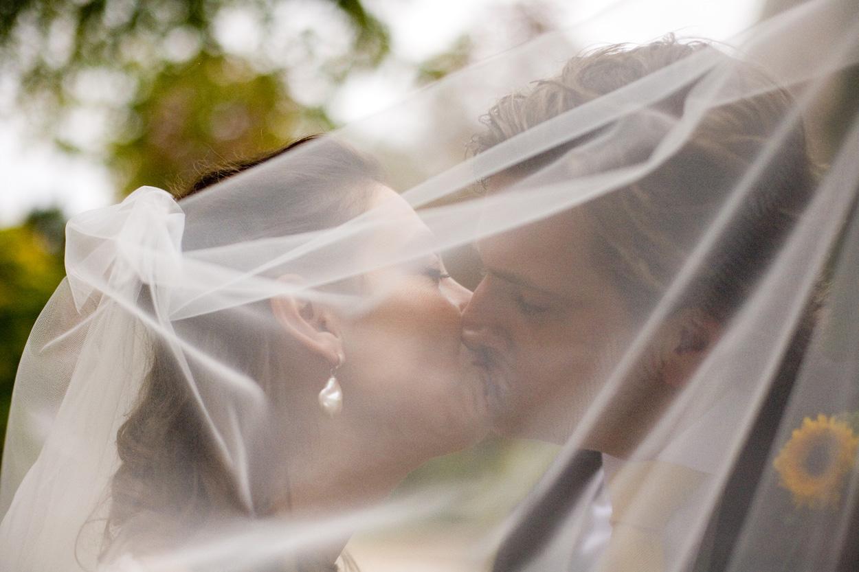Bruidsfotografie bruiloft trouwreportage rode loper kus bruidspaar sluier