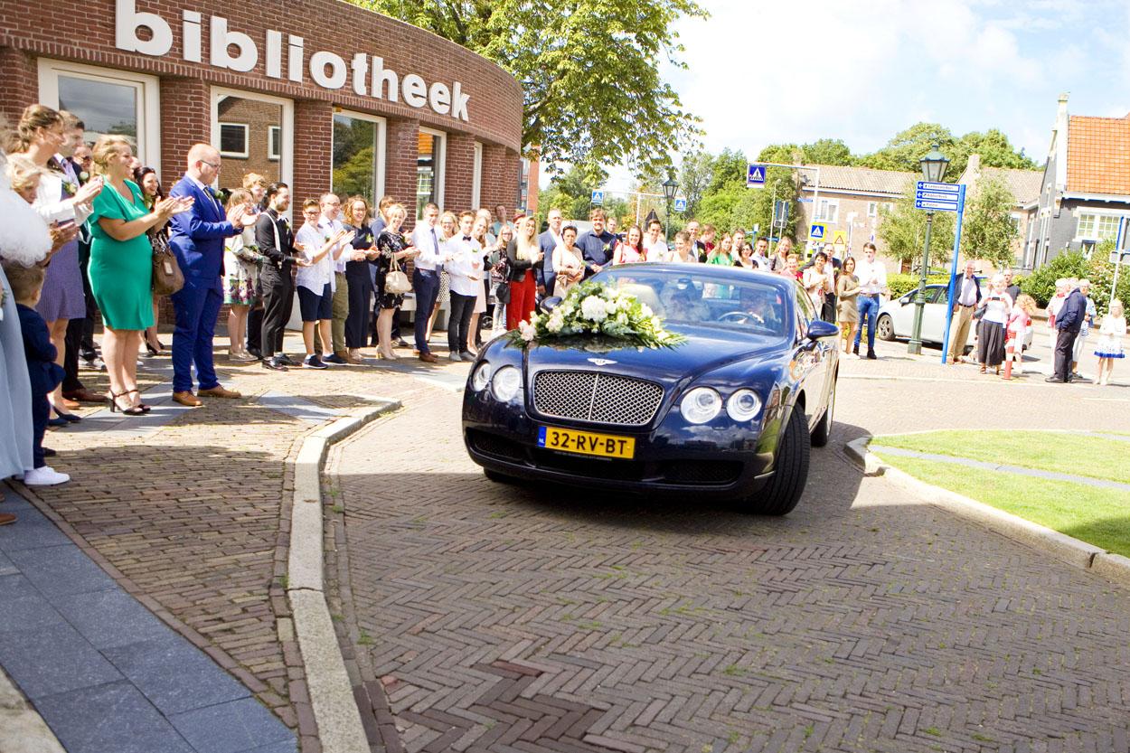 Bruidsfotografie bruiloft aankomst bruidspaar trouwauto Bentley Gemeentehuis Noordwijkerhout spontane trouwreportage