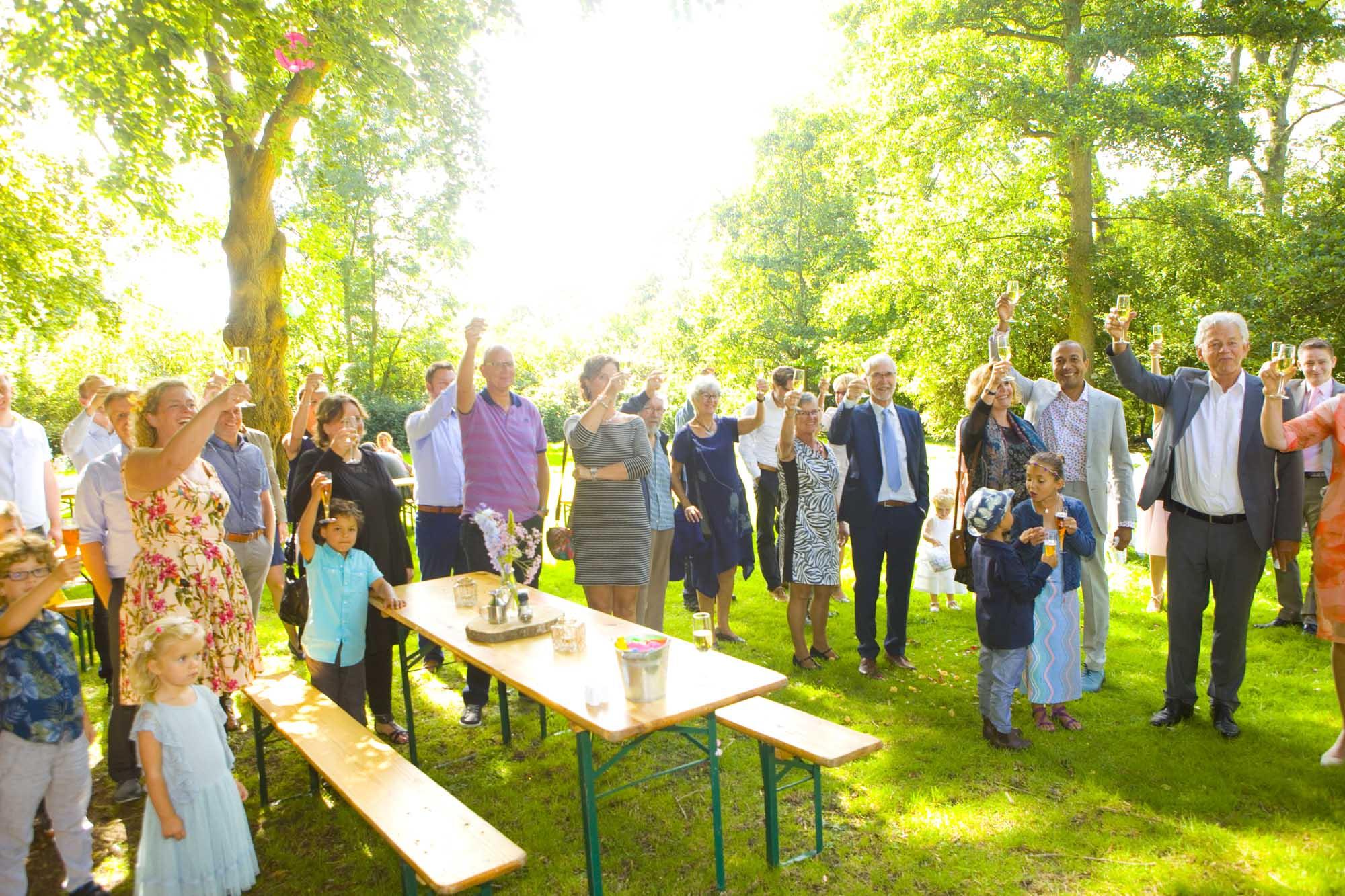 Bruidsfotografie bruiloft proosten gasten buiten Hertenhorst Delft