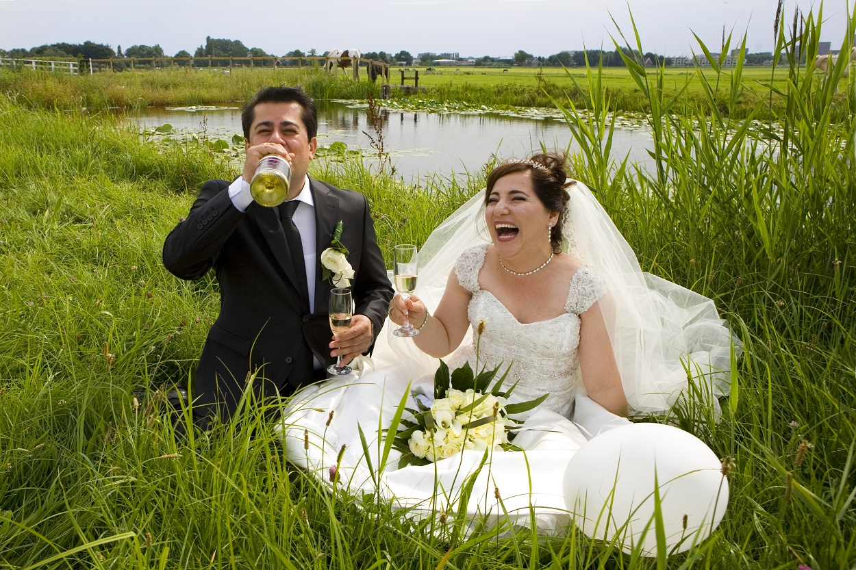 Bruidsfotografie bruidspaar schaterlach trouwreportage picknick weiland waterkant Leidschendam Molendriegang