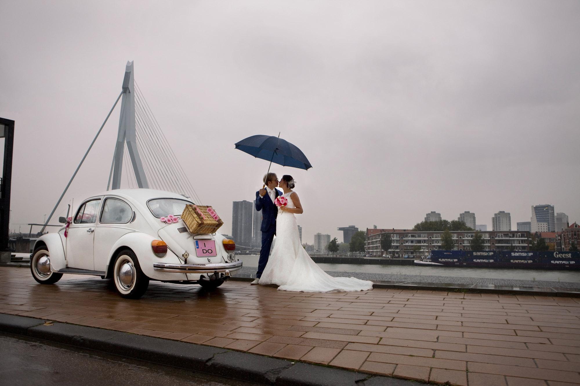 trouwreportage Maasboulevard bruidspaar regen trouwauto Volkswagen Beetle Erasmusbrug Rotterdam
