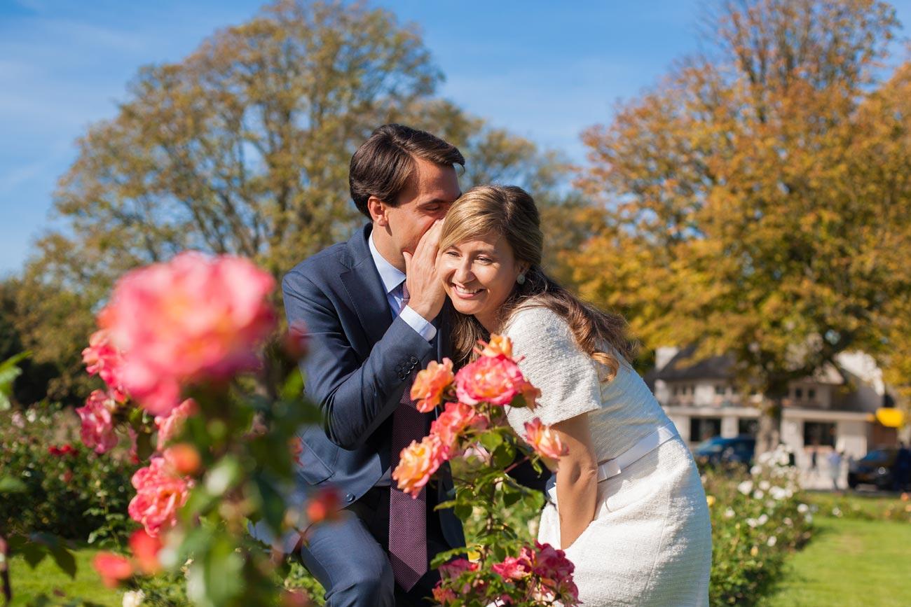 Bruidspaar in Rosarium Westbroekpark in Den Haag fluisteren in oor van bruid