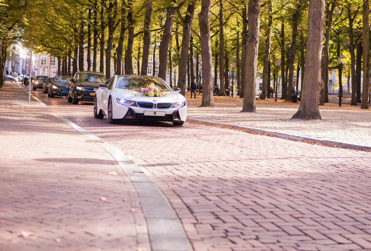 Bruidsstoet met trouwauto op Lange Voorhout in Den Haag met trouwauto BMW i8