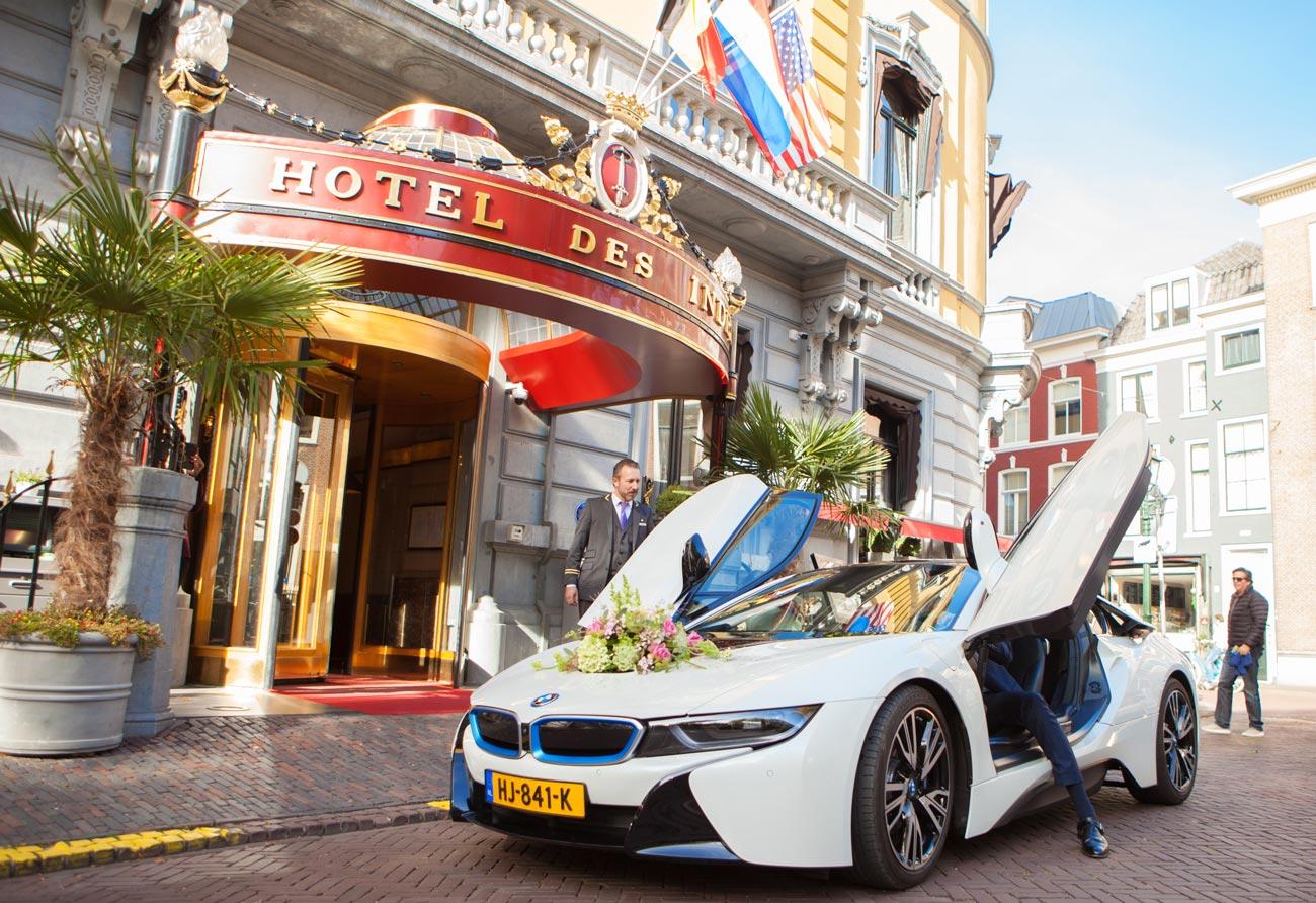 Aankomst bruidspaar met trouwauto bij Hotel Des Indes in Den Haag met trouwauto BMW i8