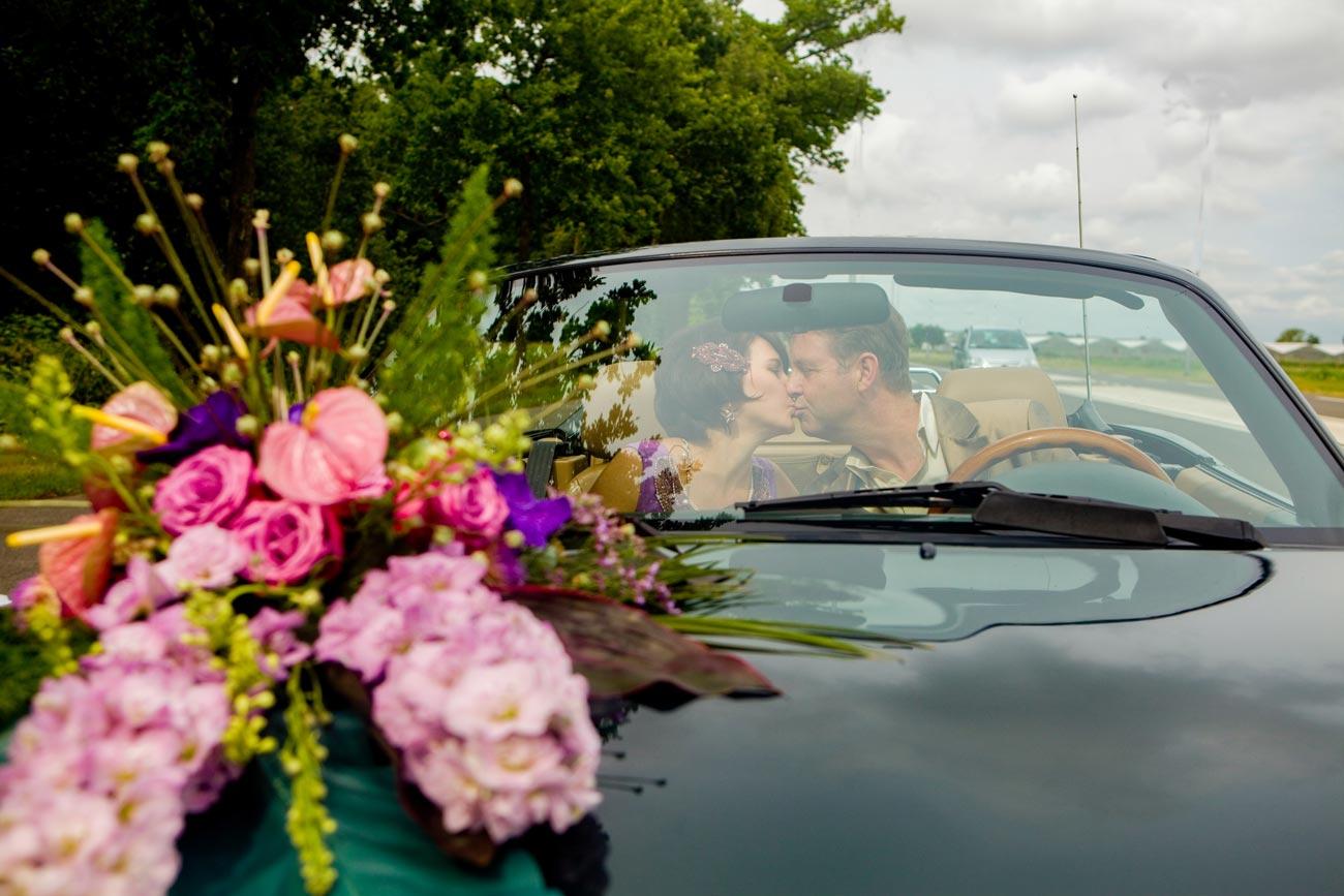 bruidspaar kus in auto met bloemstuk
